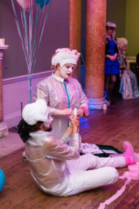 A picture of Ella and their colleague Sam. Ella is wearing a translucent jacket, pink shirt, white trousers, hot pink socks and white trainers. Sam wears a translucent jacket, white trousers and pink wellies. They are both wearing Georgian white wigs, and their faces are painted white. Ella is kneeling above Sam, who is sitting on the floor. Ella is singing to Sam, concerned and plaintive, while Sam is nursing a cut finger.