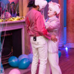 A picture of Ella and their colleague Sam. Ella is wearing a translucent jacket, pink shirt, white trousers, hot pink socks and white trainers. Sam wears a pink shirt, white trousers and pink wellies. They are both wearing Georgian white wigs, and their faces are painted white. They are holding each other and singing at each other in a flirtatious way. The background is strewn with blue and pink balloons on a fireplace.